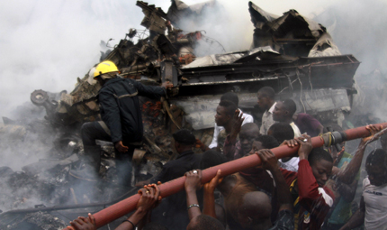 People help rescue workers lift a water hose to extinguish a fire after a plane crashed into a neighbourhood in Ishaga district